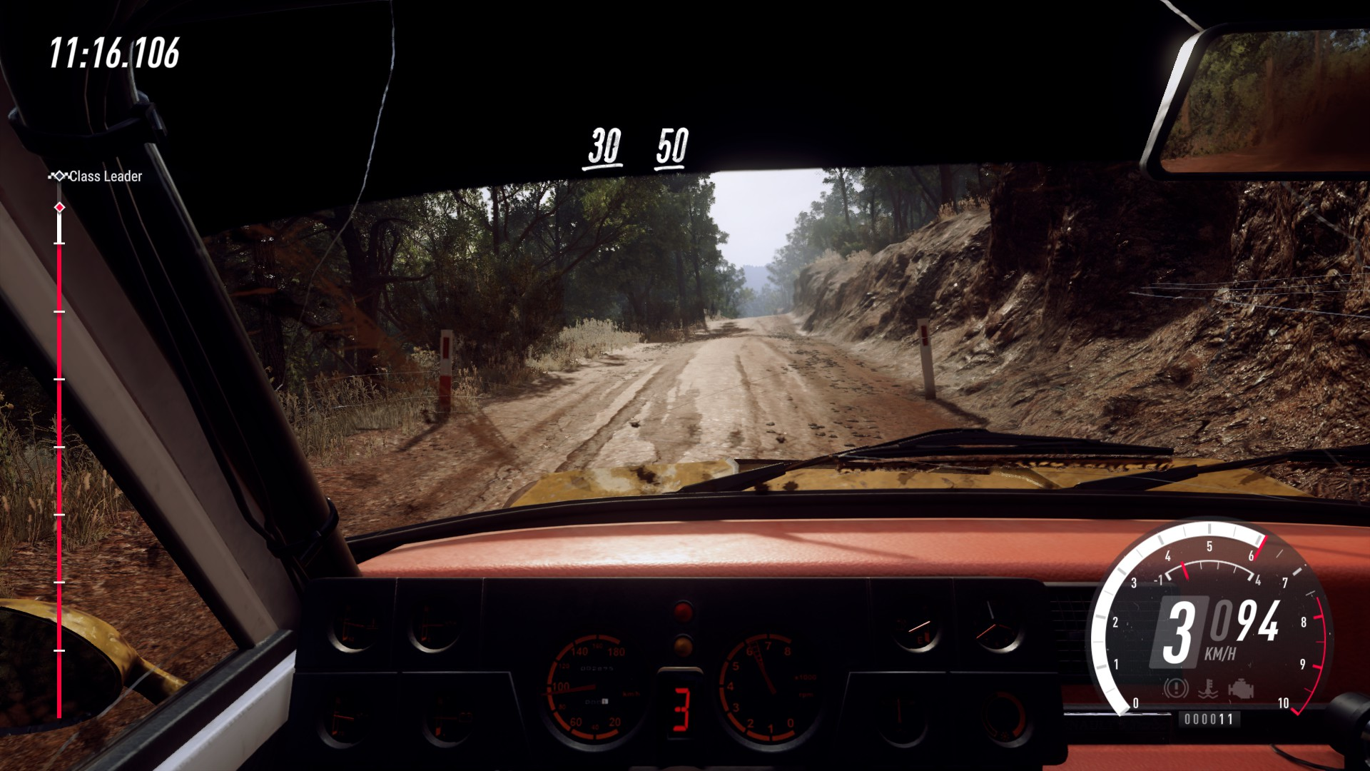 View from inside Lancia Fulvia driving down a dirt road